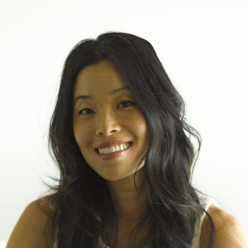 Tonia Kim smiles directly into the camera. She is a Korean woman with long black hair wearing a white shirt.