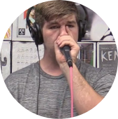 Person in a grey shirt with headphones and a microphone look at the camera.