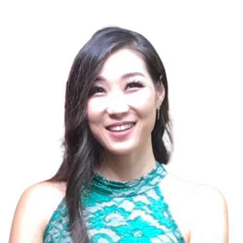 Hannah smiles directly into the camera. She is wearing a green dress and has long black hair.