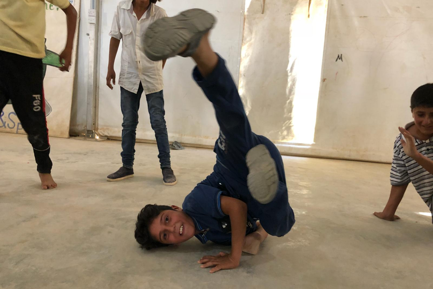 Young boy strikes a Bboy pose on a concrete floor, while two people stand to the left, and another boy dances on the floor on the right.