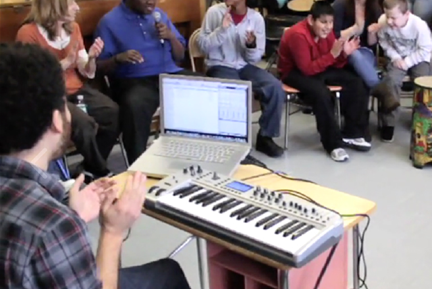 BEAT Teaching Artists sits behind a lap top and keyboard, clapping their hands, while a student beatboxes into a microphone and other students clap.