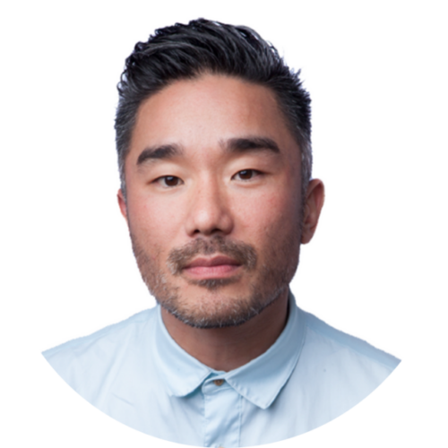James looks directly into the camera. He is a middle aged Korean-American with facial hair. He is wearing a light blue suit shirt.